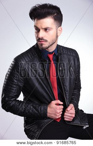 Side view picture of a casual young business man sitting on a chair, pulling his jacket.