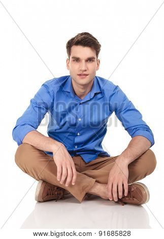 Handsome young man sitting with his legs crossed on isolated background.