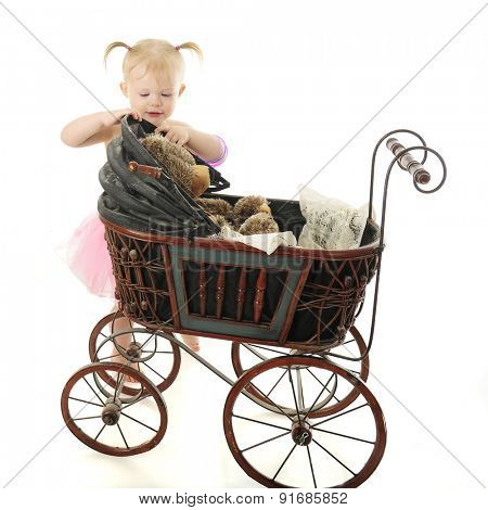 An adorable 2-year-old lifting the top of the old buggy to shade her toy bear's eyes.  On a white background.