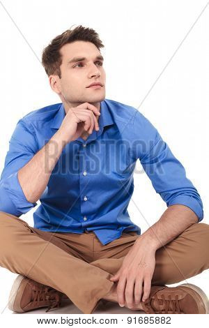 Pensive young man sitting with his legs crossed looking away from the camera, thinking.