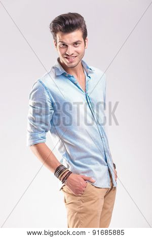 Portrait of a young casual man smiling to the camera while holding his hands in pockets.