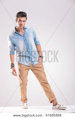 Full body picture of a casual young man posing with his hand in pocket, on grey studio background.