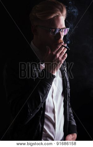 Side view of a young business man wearing a leather jacket enjoying his cigarette.