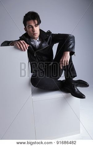Young fashion man relaxing on white furniture while looking away from the camera.