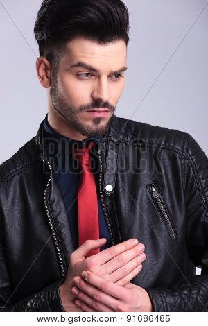 Close up picture of a young handsome business man looking away from the camera while holding his hands together.