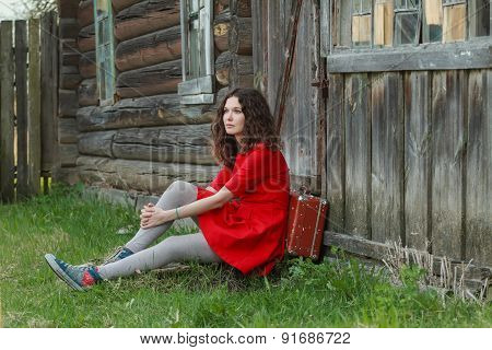 Young woman sitting on threshold of old log house with vintage suitcase