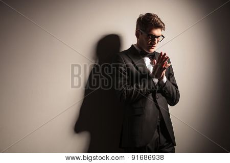 Elegant young business man holding his hands together praying.