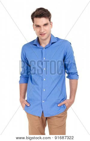 Smiling young casual man holding his hands in pockets while looking at the camera.