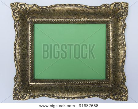antique frame painted gold on a green  background