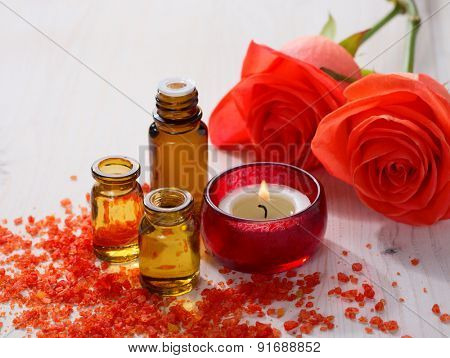 Essential oil, Mineral bath salts, candle and flowers on the wooden table.