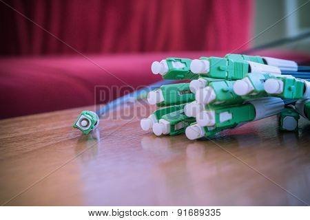 A group head connector fiber optic green color on brown table made vintage color.Fiber Optics connec