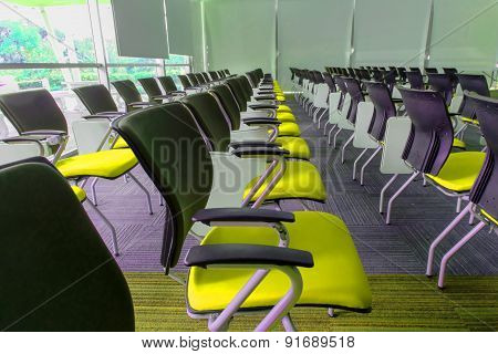 Many yellow chairs arranged neatly in a training room.