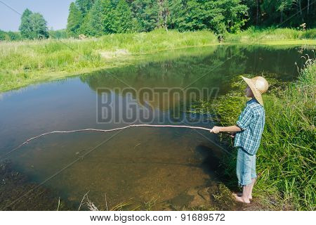 Barefoot fishing boy standing in transparent brownish waterbody