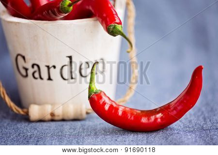 Wooden Bucket With Chili Peppers And Single One On The Side