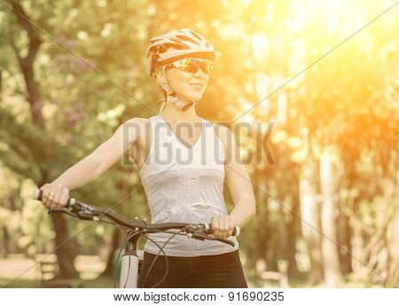 Portrait of beautiful woman in helmet with bicycle.