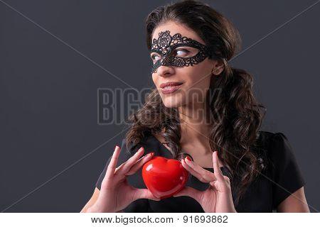 Woman wearing black mask holding heart shape