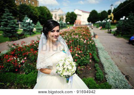 Brunette Bride With Bouquet Near The Flowers