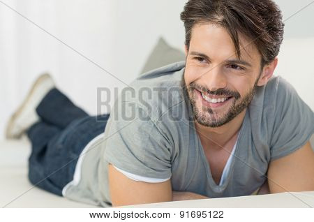 Closeup of smiling man lying on sofa in living room