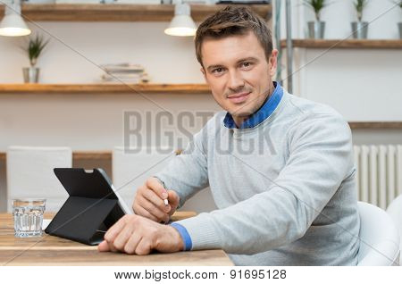 Portrait of young businessman sitting beside desk with digital tablet in office