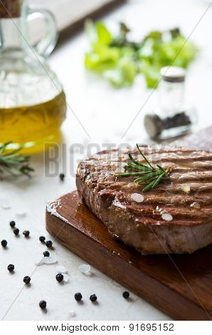Beef tenderloin cooked with rosemary and salt on cutting board