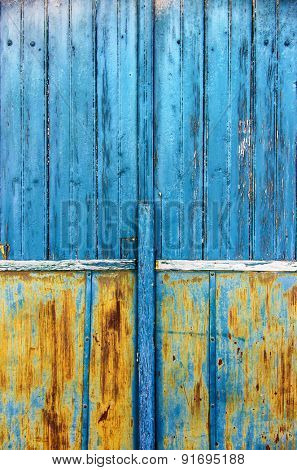 Detail of an old wooden door with scratched blue and yellow paint
