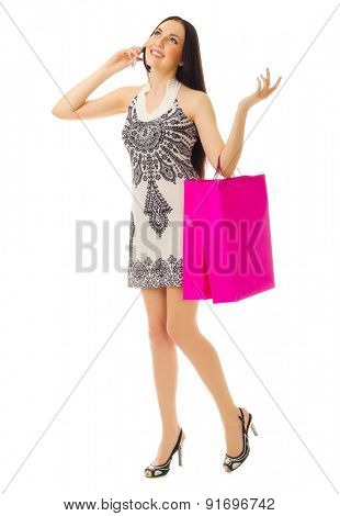 Young girl with bags talks by mobile phone isolated