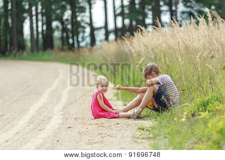 Sibling Children Playing In Dust Sitting On Summer Dirt Road