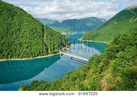 bridge on the turquoise waters of Piva Lake near Pluzine, Montenegro