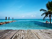 foto of infinity pool  - Swimming pool and old wooden pier in the tropical hotel - JPG