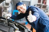 stock photo of auto garage  - Portrait of an auto mechanic at work on a car in his garage - JPG