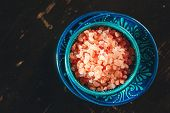 stock photo of crystal salt  - Close up of Himalayan Pink Salt Crystals in a Blue Ceramic Authentic Dishware on a Dark Wooden Surface - JPG