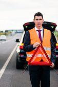 stock photo of breakdown  - Man with car breakdown erecting warning triangle on road - JPG