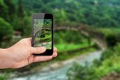 pic of plateau  - Hand holding smart phone focused on green landscape of plateau on blurry background - JPG