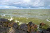 foto of dike  - Deteriorating weather over a dike along a sea in spring - JPG