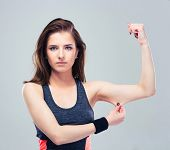 picture of biceps  - Fitness woman pinch a fat on her biceps over gray background - JPG