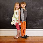 stock photo of innocence  - Little boy and girl standing back to back in front of blackboard looking at camera smiling - JPG