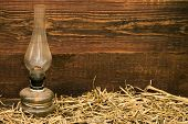foto of petroleum  - petroleum lamp with hay on rustic wooden planks background - JPG