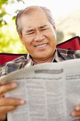 stock photo of hairline  - Senior Asian man reading outdoors - JPG