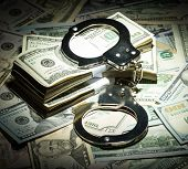 foto of handcuff  - Handcuffs on dollar money bills in spot light - JPG