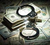 stock photo of handcuff  - Handcuffs on dollar money bills in spot light - JPG