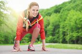 foto of track field  - Attractive blonde woman running on track outdoors fitness sport training and lifestyle concept - JPG
