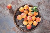 foto of apricot  - Fresh apricots in wooden bowl on old rustic background decorated with mint and lavender flower - JPG