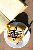 picture of treble clef  - Cups of cappuccino with treble clef on foam  and book on table in cafe - JPG