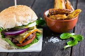 picture of burger  - serving homemade burger with potato wegdes on wooden table - JPG