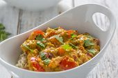 picture of curry chicken  - chicken curry red pepper and coriander leaves with rice in a white bowl - JPG