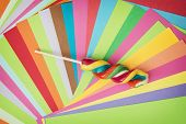picture of lollipops  - Colorful twisted sweet lollipop and brightly colored papers background - JPG