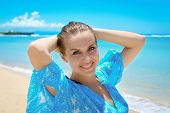 stock photo of young woman posing the camera  - Young attractive woman posing and smiling at camera in front of sea shore - JPG