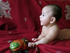 picture of baby frog  - Baby boy lies on the Indian silver embroidered dark-cherry shawl with painted box-toy frog ** Note: Soft Focus at 100%, best at smaller sizes - JPG