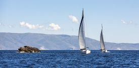 image of sailing vessels  - Two sailing boats yacht or sail regatta race on blue water Sea - JPG