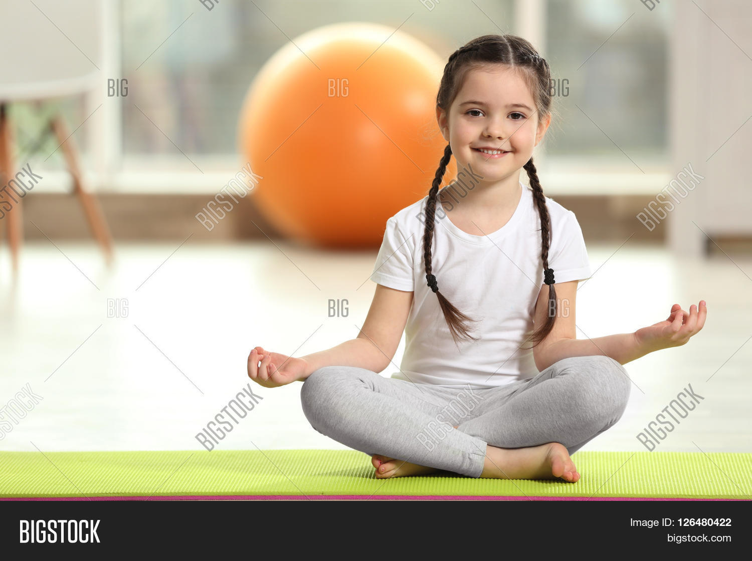 Little Cute Girl Practicing Yoga Pose On A Mat Indoor